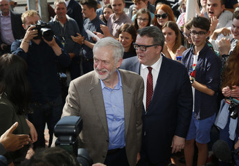 Britain's Labour Party leader Jeremy Corbyn and deputy leader Tom Watson greet supporters at the beginning of the annual Labour Party Conference in Brighton
