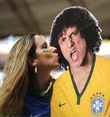 A fan poses with a picture of Brazil's David Luiz before the 2014 World Cup third-place playoff between Brazil and the Netherlands at the Brasilia national stadium