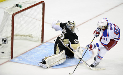 Penguins goaltender Fleury makes a save against Rangers' Nash in the overtime shootout of their NHL hockey game in Pittsburgh