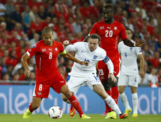 Switzerland's Inler and Djourou challenge England's Rooney during their Euro 2016 qualifying soccer match at the Sankt Jakob-Park stadium in Basel