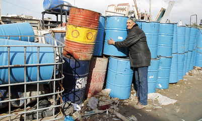 A man stacks discarded oil barrels at a scrap metal yard in Tunis