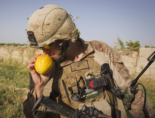 Creed Taylor, U.S. Marines Corporal of the Weapons Company, 1st Battalion, 3rd Marines, smells melon given to him by local farmer during joint patrol with Afghan National Army soldiers near Patrol Base Karma in Helmand province