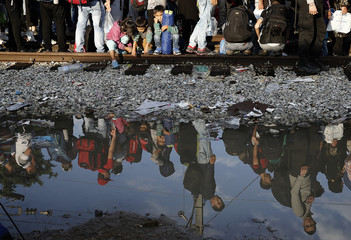 Syrian refugees are reflected in a puddle as they wait at the Greek-Macedonian border