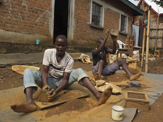 Artisanal miners crush tin ore before it is washed and then bagged ready for sale in Nyabibwe