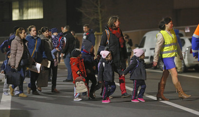 Children are released from their school near the scene where shots were fired during a police search of a house in the suburb of Forest near Brussels