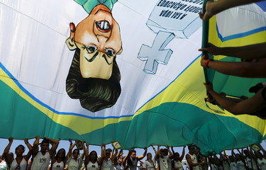 Demonstrators wave a flag with a draw of Brazil's President Dilma Rousseff during an anti-government demonstration in Copacabana in Rio de Janeiro