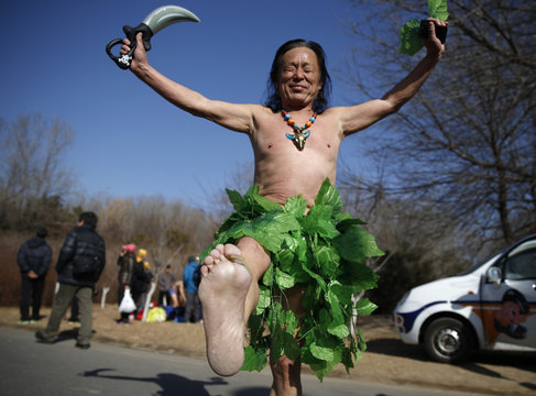 """A man who completed the """"Half-Naked Marathon"""" barefoot shows his right sole at a park in Beijing"""