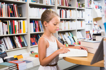 little smart girl reading a book in school library