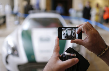 A man uses his mobile phone to take a picture of an Aston Martin car used by Dubai police at the Arabian Travel Market exhibition in Dubai