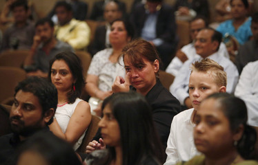 A South African expatriate cries during a memorial service ceremony for the late former South African President Mandela in Mumbai