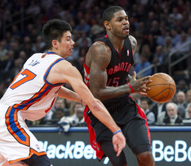 Toronto Raptors Amir Johnson tries to carry ball past New York Knicks Jeremy Lin in NBA game in New York