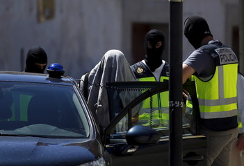 A suspect is led by Spanish National Police officers after being arrested in San Martin de la Vega
