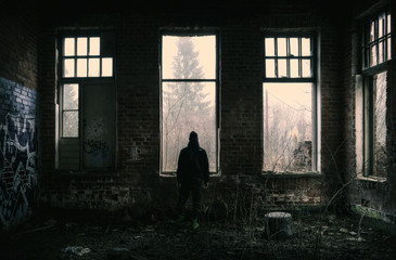Lonely depressed man standing at dark abandoned factory.