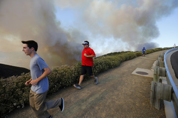 After climbing a hillside to view the so-called Poinsettia Fire, residents are evacuated by police near San Marcos, California