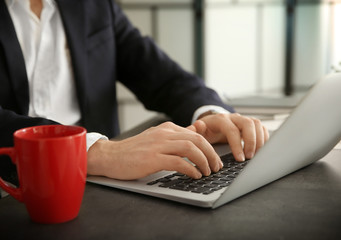 Young businessman working with laptop in office, closeup