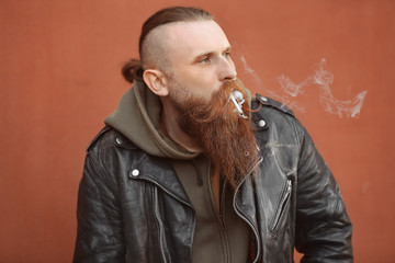 Bearded man smoking weed outdoors on color background