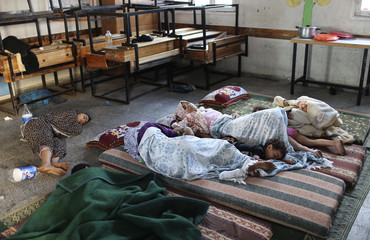 Palestinians, who according to a family member fled their home after being warned by Israel of an impending air strike on their house, sleep as they stay at a school in Rafah in the southern Gaza Strip