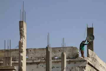 A man fixes a satellite dish over a damaged house after air strikes yesterday in the rebel-held town of Dael, in Deraa Governorate