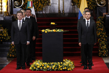 Colombia's President Juan Manuel Santos and his Mexican counterpart Enrique Pena Nieto stand next to an urn containing the ashes of late Colombian Nobel laureate Gabriel Garcia Marquez in Mexico City