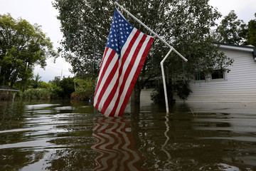 An American flag is seen waving above flood waters in Sorrento