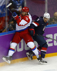Team USA's Parise hits Russia's Yemelin during the first period of their men's preliminary round ice hockey game at the 2014 Sochi Winter Olympics