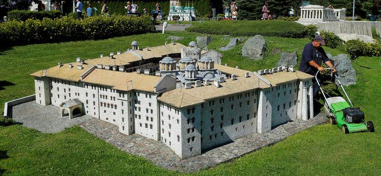 A gardener mows the lawn around a scale model of Bulgaria's Rila Monastery in Minimundus theme park in Klagenfurt