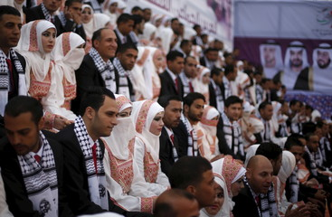 Palestinian grooms sit with their brides on the stage during a mass wedding for 200 couples in Gaza City