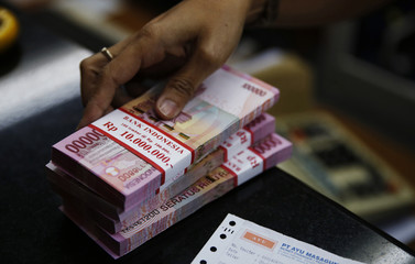 A money changer holds stacks of Indonesian rupiah notes in Jakarta