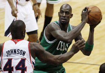 Celtics forward Garnett holds the ball while guarded by Hawks forward Johnson in the first half of their NBA Eastern Conference playoffs basketball game in Atlanta