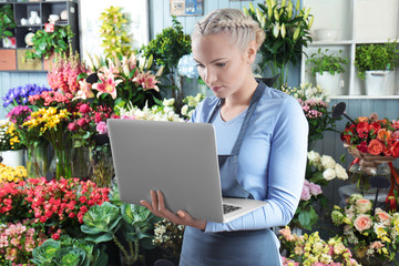 Beautiful female florist with laptop in flower shop