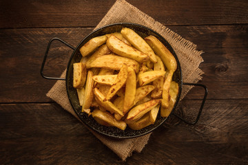 Crunchy roasted potatoes in skillet on dark rustic texture