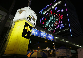 An artwork of a yellow umbrella, symbol of the Occupy Central movement, is seen on a road sign next to a protest site in front of a commercial building with Christmas decorations, at the financial Central district in Hong Kong