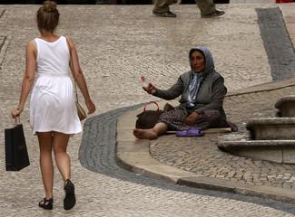 A woman begs on a street in downtown Lisbon