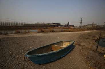 A boat is seen on the ground next to a fish farm located near an abandoned steel mill of Qingquan Steel Group in Qianying township