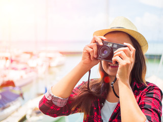 Close up Portrait of beautiful woman happy and smile with retro hipster camera having fun at the beach.