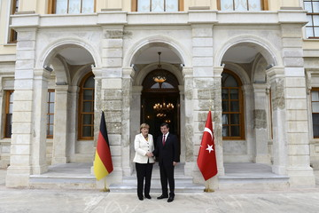 Turkish Prime Minister Ahmet Davutoglu shakes hands with German Chancellor Angela Merkel before their meeting in Istanbul, Turkey