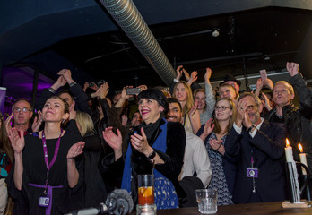 Jonsdottir of the Pirate Party reacts alongisde party members after early results of the parliamentary elections in Iceland