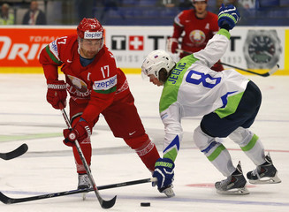 Slovenia's Jeglic fights for the puck with Belarus' Kalyuzhny during their Ice Hockey World Championship game at the CEZ arena in Ostrava