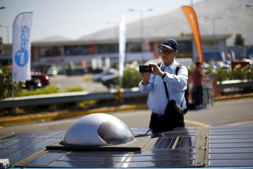 "A man uses his mobile phone to take pictures of a solar-powered car on display during an event to test cars participating in the ""Atacama solar race"" in Santiago"