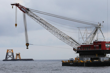 Construction crane floats next to a barge carrying jacket support structures and a platform for a turbine for a wind farm in the waters of the Atlantic Ocean off Block Island, Rhode Island
