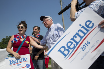Democratic presidential hopeful Sen. Bernie Sanders takes photos with supporters during the Independence Day Parade in Creston, Iowa