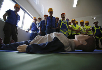 Participants look at a dummy as they learn about CPR procedure during an electric shock accident at an experience centre for construction safety training in Beijing