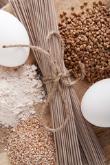 Products made from buckwheat on a wooden table: noodles (soba), buckwheat, flour and cereals..