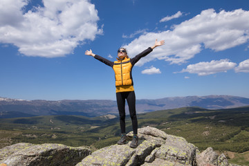 sport hiking or trekking woman with yellow jacket, standing on rock peak, with arms up and happy face, behind Lozoya Valley and Guadarrama Park, in Madrid, Spain