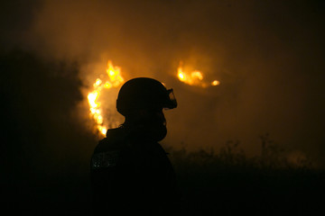 Israeli fire-fighter works to extinguish a fire caused by rockets launched from the Gaza Strip towards Israel near the town of Sderot