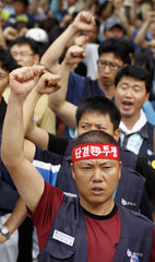 Workers of the Hyundai-Kia Automotive Group labour unions chant slogans at a rally in Seoul