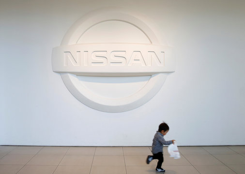A child runs past the Nissan brand logo in the showroom at the carmaker's headquarters in Yokohama
