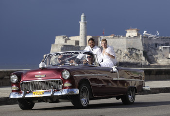 Bride and groom ride U.S.-made 1955 Chevrolet on Havana's seafront boulevard 'El Malecon' with Spanish colonial era fortress 'El Morro' in the background during wedding celebration