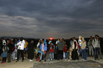 Syrian refugees line up at a police checkpoint at Greece's border with Macedonia, near the Greek village of Idomeni