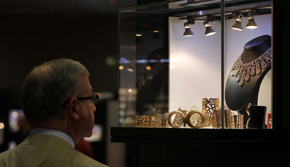 Visitor looks at gold jewellery on stand at Valenza international jewels exposition in Valenza